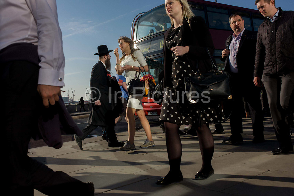 Londoners cross southbound over London Bridge during the evening rush hour. People merge on this busy crossing point including an Orthodox Jewish man in black and a woman is a short skirt. Commuters stride alongside others walking out of the City of London. There has been a crossing over the Thames here since the Romans first forded the river in the early 1st Century with subsequent medieval and Victorian stone bridges becoming an important thoroughfare from the City on the north bank, to Southwark on the south where transport hubs such as the mainline station gets commuters to the suburbs and satellite towns.