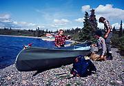 Backcountry Park Ranger Cheryl Bloethe Linder assisting two German men in assembling their collapsible canoe, Lower Twin Lake, Lake Clark National Park, Alaska.