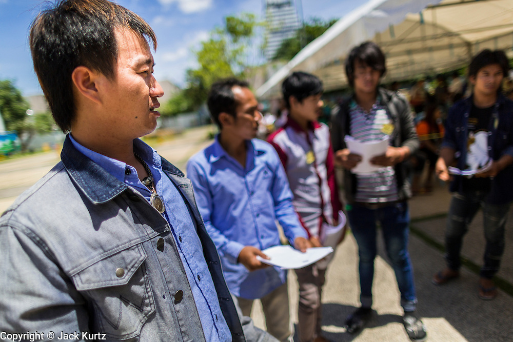 """17 JULY 2014 - BANGKOK, THAILAND: Undocumented Cambodian men apply for work permits at the temporary """"one stop service center"""" in the Bangkok Youth Center in central Bangkok. Thai immigration officials have opened several temporary """"one stop service centers"""" in Bangkok to register undocumented immigrants and issue them temporary ID cards and work permits. The temporary centers will be open until August 14.    PHOTO BY JACK KURTZ"""