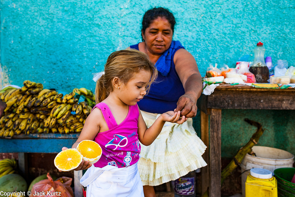 09 JANUARY 2007 - GRANADA, NICARAGUA: A woman gives her daughter some fruit from her stand on the street in Granada, Nicaragua. Granada, founded in 1524, is one of the oldest cities in the Americas. Granada was relatively untouched by either the Nicaraguan revolution or the Contra War, so its colonial architecture survived relatively unscathed. It has emerged as the heart of Nicaragua's tourism revival.  Photo by Jack Kurtz