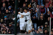 Wilfried Bony of Swansea City (l)celebrates with Ki Sung-Yueng of Swansea City after scoring his teams first goal of the match to make it 1-0. Barclays Premier league match, West Ham Utd v Swansea city at the Boleyn ground, Upton Park in London on Sunday 7th December 2014.<br /> pic by John Patrick Fletcher, Andrew Orchard sports photography.
