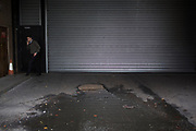 Office worker steps outside to smoke a cigarette outside some garage doors in the City of London. UK.