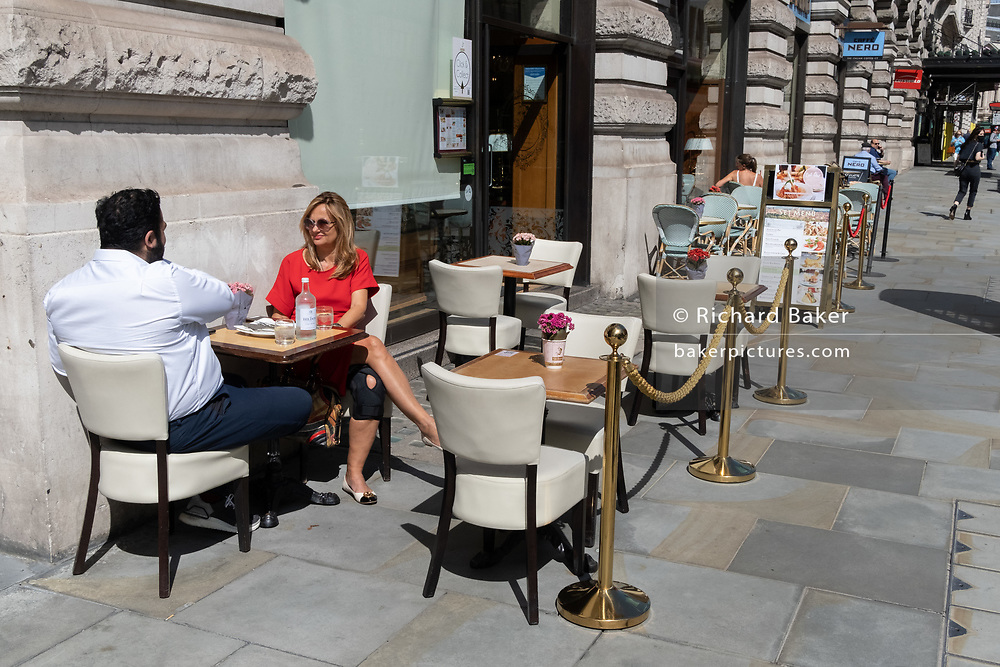 A man and lady occupy a table outside a Piccadilly bar during the Coronavirus pandemic, on 20th August 2020, in London, England