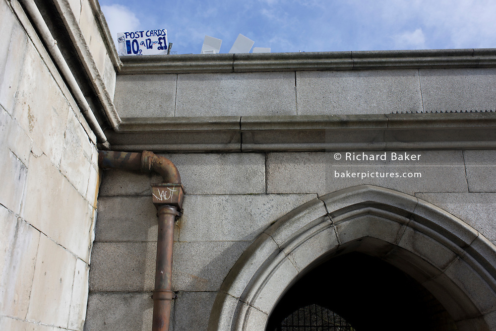 A tourism postcard sign above a drainpipe at the underpass beneath Westminster Bridge on London's Southbank,