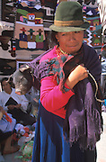 ECUADOR, MARKETS Otavalo, woman with pig in shawl