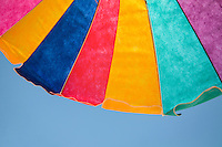 Colorful beach umbrella with blue sky.