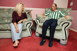 Man with Parkinsons disease in chair fitted with chairraising blocks; talking to his daughter,