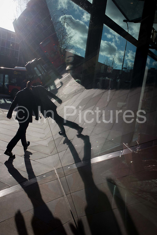Angled passer-by reflections in sheet glass of City office entrance. A man walks along this city street with strong sunshine just over the roofs of buildings opposite. He strides along with his shadow forming the bottom of the picture, near the windows of a corporate office foyer whose red seat is seen on the right. The view is angled to let the straight lines become diagonals that cross the photo, in the heart of the capital's financial centre, founded by the Romans in 43AD.