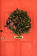 The wooden doorway of a historic home decorated with a Magnolia leaf Christmas wreath on Meeting Street in Charleston, SC.