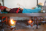 """Yu Sokna and her baby undergoing """"Ang Pleung"""" - Postpartum heating procedure: After giving birth a woman is carried by her husband to a wood or bamboo bed under which a fire has been built. The women has a bag of ice on her navel. Meanwhile a Traditional Healer or Birth Attendant recites Buddhists texts while walking around the bed to protect the woman from evil spirits. In the past it was considered important to use a certain mix of woods to protect against supernatural forces and produce a smoke that eased the pain of childbirth. At the present time most women appear to prefer to use charcoal as it is smoke free, but may be more toxic...Touth Koeun, an ex-Khmer Rouge child soldier turned midwife and trainer, is on the frontline again, but this time campaigning on maternity issues, in Preah Vihear province, Cambodia. The country experiences an extraordinarily high incidence of infant and maternal mortality. The Preah Vihear province, in Cambodia's north, bordering on the Thai border, can be described as an outback rural area, villages often many hours away from a health centre or clinic, and sometimes near the frontline where soldiers and their families are living. Here, Touth Kouen, a locally much respected pioneer and experienced in maternity issues, trains indigenous women, known as 'Traditional Birth Attendants' (TBA's), correct procedures to assist midwives and nurses, to give direct support to mothers and their babies, during ante and post natal periods. Traditional bush medicine and spiritual practices by 'Kruu' bush doctors, involving the killing of endangered species, gathering herbs and plants, whose burnt remains are often ground up into unhealthy potions, and fed to mothers as miracle cures, and postpartum heating, can cause illness and death. The Kruu, and local people in general need to be re-educated, so as to create a healthy nurturing environment for mothers and their babies. Preah Vihear Province, Cambodia"""