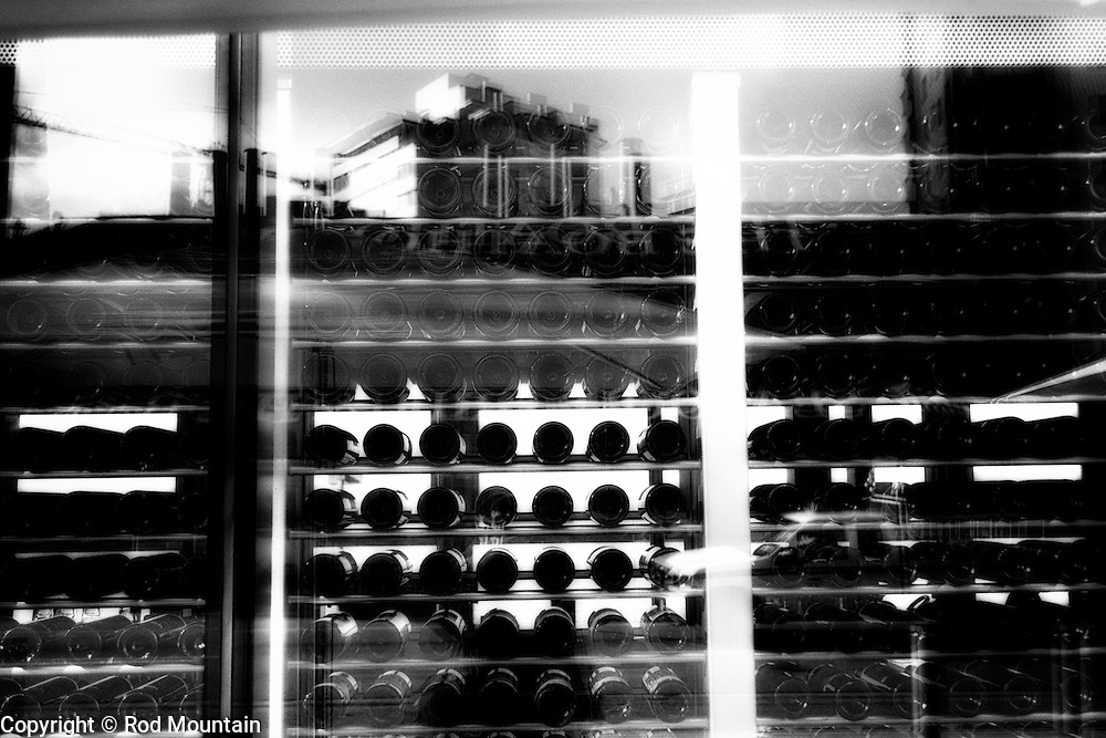 Through a window, a restaurant's wine collection is seen in the mix of reflections. Photo: © Rod Mountain