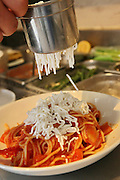 Preparing Spaghetti and marinara sauce adding the Parmesan Cheese