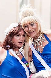 © Licensed to London News Pictures. 27/06/2015. Trafalgar Square, London, UK.  A pair of drag queens are amongst the crowd watching participants take part in the annual Pride parade in London, one of the world's largest LGBT+ events.  Hundred of thousands of people gathered to watch the events on a hot summer's afternoon. Photo credit : Stephen Chung/LNP
