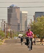 South Tucson resident Alba Davis cycles to work on a Sunday morning through the southside community, Tucson, Arizona, USA.