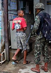 Soldados do Exército Brasileiro revistam moradores na entrada da favela Morro do Alemão, em 27 de novembro de 2010 no Rio de Janeiro, Brasil.. Centenas de soldados e policiais se juntaram para uma repressão sobre as gangues de drogas. No início desta semana, a polícia forçou os membros das gangues saírem da favela Vila Cruzeiro, com o auxílio de tanques M113 transportadores blindados de pessoal. FOTO: Jefferson Bernardes/Preview.com