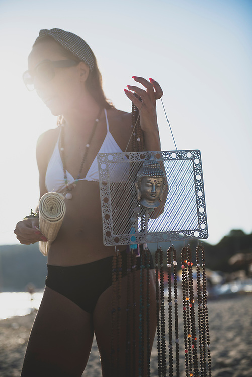 Salinas Beach, Ibiza, Spain - August 4, 2018: A woman sells necklaces to beachgoers at Salinas Beach on the southern end of Ibiza.