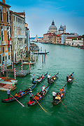"Six gondolas on Venice's iconic Canal Grande canal<br /> .....<br /> Venice is a city in northeastern Italy sited on a group of 118 small islands separated by canals and linked by bridges. It is located in the marshy Venetian Lagoon which stretches along the shoreline, between the mouths of the Po and the Piave Rivers. Venice is renowned for the beauty of its setting, its architecture and its artworks. The city in its entirety is listed as a World Heritage Site, along with its lagoon. Venice is the capital of the Veneto region. In 2009, there were 270,098 people residing in Venice's comune. Although there are no historical records that deal directly with the founding of Venice, tradition and the available evidence have led several historians to agree that the original population of Venice consisted of refugees from Roman cities near Venice such as Padua, Aquileia, Treviso, Altino and Concordia (modern Portogruaro) and from the undefended countryside, who were fleeing successive waves of Germanic and Hun invasions. Some late Roman sources reveal the existence of fishermen on the islands in the original marshy lagoons. They were referred to as incolae lacunae (""lagoon dwellers""). The traditional founding is identified with the dedication of the first church, that of San Giacomo at the islet of Rialto (Rivoalto, ""High Shore""), which is said to have been at the stroke of noon on 25 March 421."