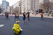 A volunteer watches runners pass by during the 10th Tokyo Marathon took place on a fine spring day in Tokyo Japan. Sunday February 28th 2016. Thirty-six thousand runners took part with Ethiopian,  Feyisa Lilesa winning the  men's competition and  Kenyan, Helah Kiprop victorious in the women's race.