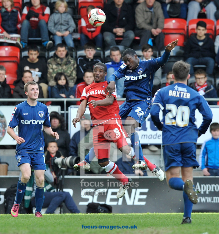 Picture by Alan Stanford/Focus Images Ltd +44 7915 056117.27/04/2013.Kevin Lisbie of Leyton Orient and Glenn Belezika (27) of Oldham Athletic challenge for the header  during the npower League 1 match at the Matchroom Stadium, London.. .
