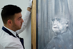 © Licensed to London News Pictures. 14/06/2013. London, UK. A member of Sotheby's staff looks at Francis Bacon's 'Head III' (1949, est. GB£5,000,000-7,000,000), the first portrait ever sold by the British artist, at the press view for a Sotheby's auction in London today (14/06/2013). The Contemporary Art Evening Sale takes place on the 26th of June 2013 at Sothery's New Bond Street premises.  Photo credit: Matt Cetti-Roberts/LNP