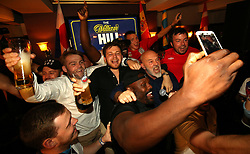 Dereck Chisora takes a picture as Fat Les (centre right) performs at the Lord Raglan Pub in London.