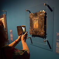 Visitors takes photos with her mobile phone of an artwork by Mexican painter Frida Kahlo titled Survivor seen on display at the Frida Kahlo exhibition in the National Gallery in Budapest, Hungary on July 5, 2018. ATTILA VOLGYI