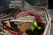 An amployee for UK Power Networks prepares high-voltage underground cables in central London with reflective corporate backdrop behind. Standing in a sub-pavement level hole on Victoria Street, Westminster the man bends and cuts to size these red coloured protective collars that will deliver efficient power to nearby government and company buildings. reflected in the highly-polished surfaces behind are the fencing and Londoners passing-by.