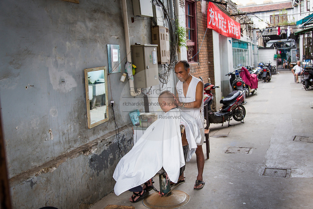A barber cuts hair in an alley in Shanghai, China