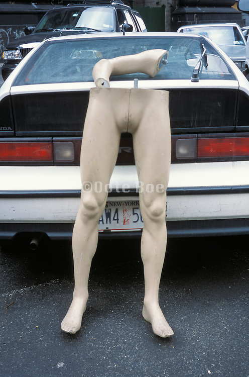 mannequin legs and parts against a car