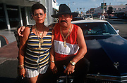 A portrait of an exiled Cuban couple sitting on the hood, or bonnet of their car in Miami Beach, on 15th May 1996, in Miami, Florida USA.