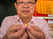 """22 APRIL 2014 - WANG NUA, LAMPANG, THAILAND: Mr. WATTASIN, owner of the gold shop in Wang Nua, holds piece of gold mined from the Mae Wang. He buys gold from the villagers who mine the riverbed for gold. Villagers in the Wang Nua district of Lampang province found gold in the Mae Wang (Wang River) in 2011 after excavation crews dug out sand for a construction project. A subsequent Thai government survey of the river showed """"a fair amount of gold ore,"""" but not enough gold to justify commercial mining. Now every year when the river level drops farmers from the district come to the river to pan for gold. Some have been able to add to their family income by 2,000 to 3,000 Baht (about $65 to $100 US) every month. The gold miners work the river bed starting in mid-February and finish up  by mid-May depending on the weather. They stop panning when the river level rises from the rains. This year the Thai government is predicting a serious drought which may allow miners to work longer into the summer.    PHOTO BY JACK KURTZ"""