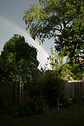 Rainbow over trees in a residential back garden in Moseley on 13th June 2020 in Birmingham, United Kingdom. Moseley is a suburb of south Birmingham, England, 3 miles south of the city centre. The area is a popular cosmopolitan residential location known for its large houses and leafy streets.