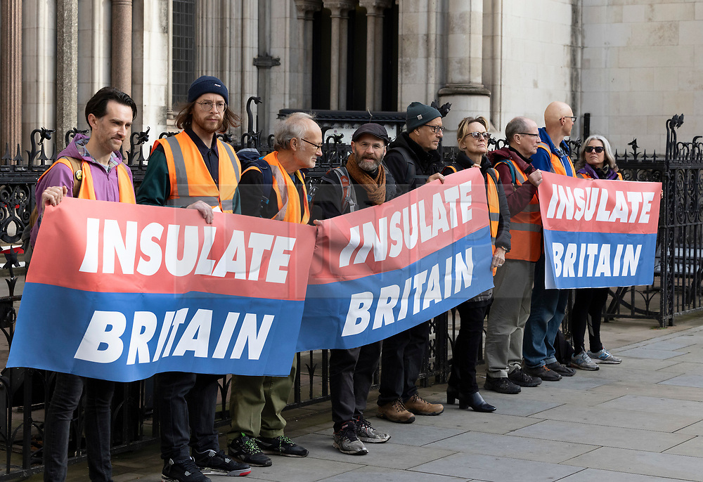 © Licensed to London News Pictures. 05/10/2021. London, UK. Activists from Insulate Britain climate change protest group stand with banners at the High Court in central London. Lawyers for the government are seeking enforce injunctions brought to stop activists actions in blocking traffic on the road network. Home Secretary Priti Patel is expected to warn protestors they could face unlimited fines and up to six months in jail. Police will also be given powers to stop and search activists for equipment used to prevent them from being cleared from the road such as glue and locks. Photo credit: Peter Macdiarmid/LNP