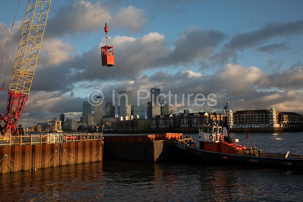 Workers are craned out in a red cage from deep down as Construction work continues on the Thames Tideway Tunnel or Super Sewer on the River Thames on 18th November 2019 in London, England, United Kingdom. The Thames Tideway Tunnel is an under-construction civil engineering project 25 km tunnel running mostly under the tidal section of the River Thames through central London, which will provide capture, storage and conveyance of almost all the combined raw sewage and rainwater discharges that currently overflow into the river.