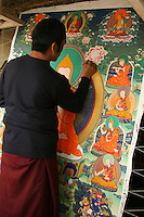 Painting a Mandala at Dropeling in Lhasa, a cooperative to aid native Tibetan artists and artisans -  Thangka Painters -  A thangka is a painted or embroidered Buddhist banner which is hung in a monastery or a family altar and occasionally carried by monks in ceremonial processions. Sometimes a thangka is called a scroll painting.  Originally, thangka painting became popular among traveling monks because the scroll paintings were easily rolled and transported from monastery to monastery. These thangka served as important teaching tools depicting the life of the Buddha, various influential lamas and other deities and bodhisattvas. One popular subject is The Wheel of Life.