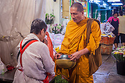 09 OCTOBER 2012 - BANGKOK, THAILAND:  A Buddhist monk collects alms in the Bangkok Flower Market. Most males in Thailand enter the Sangha (become Buddhist monks) at least once in their lives. Their time in the Sangha may be as short as a few weeks or as long as a lifetime commitment. The Bangkok Flower Market (Pak Klong Talad) is the biggest wholesale and retail fresh flower market in Bangkok. It is also one of the largest fresh fruit and produce markets in the city. The market is located in the old part of the city, south of Wat Po (Temple of the Reclining Buddha) and the Grand Palace.    PHOTO BY JACK KURTZ