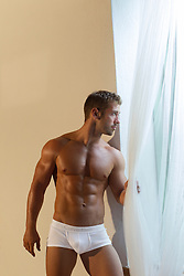 muscular man in underwear at home looking out a large window