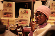 A woman has a bite of some chocolate at a book signing for a book named Harlem.  Harlem, a neighborhood of New York City in Manhattan, began as a Dutch village in 1658 and was later annexed to New York City in 1873.  At the beginning of the 20th century African-American's began arriving from the southern American states looking for work in the more industrious north.  With their migration, the African-American community brought with them a renaissance in the arts to Harlem that is still evident today.  After World War II Harlem began experiencing a significant rise in crime and poverty due to the Great Depression that lasted until the 21st century.  A new pride in the community has brought a renewed revival to Harlem, and crime rates have dropped to record lows giving the New York City neighborhood a new lease on life.