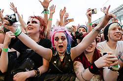 © Licensed to London News Pictures. 01/06/2013. London, UK.   Green Day fans wearing punk make-up cheer as the band performs live at The Emirates Stadium. Green Day is an American punk rock band formed in 1987. The band consists of lead vocalist and guitarist Billie Joe Armstrong, bassist and backing vocalist Mike Dirnt, drummer Tré Cool and guitarist and backing vocalist Jason White.  Photo credit : Richard Isaac/LNP