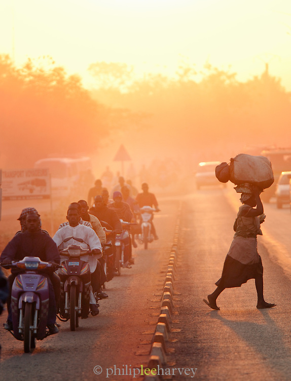 A woman dashes across a busy main road. Thousands of people ride in the mornings on their mopeds, a time called Moped Mania, in Bamako, Mali