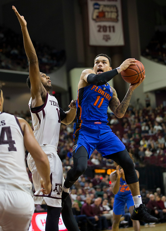 Florida guard Chris Chiozza (11) looks pass against Texas A&M center Tonny Trocha-Morelos (10) during the second half of an NCAA college basketball game Tuesday, Jan. 2, 2018, in College Station, Texas. (AP Photo/Sam Craft)