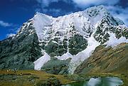 Trekkers picnic beneath snowy Rondoy Peak (5870 m or 19,260 feet), in the Cordillera Huayhuash, Andes Mountains, Peru, South America.