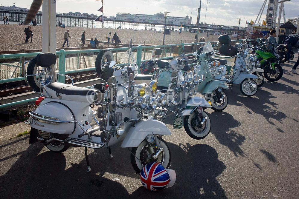 Vespa scooters on display on Brighton's seafront esplanade on Bank Holiday weekend. Fitted to the frame of the bike are many headlights and mirrors that is the cultural ephemera of the British mod subculture of the 1960-70s. Locked to the front wheel is a beautifully painted helmet with a union jack flag design. Focused on music and fashion, mods have their roots in a small group of London-based stylish young men in the late 1950s who were termed modernists because they listened to modern jazz. Traditionally they gathered at seaside towns on the south coast, like Brighton where clashes with Rockers was a Bank Holiday weekend tradition.