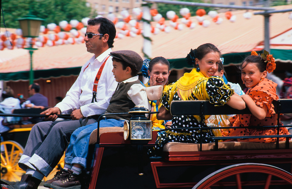 "Europe, Spain, Andalucia, Sevilla, family riding in horse-drawn carriage during ""Feria de Abril"" festival, held annually in April"