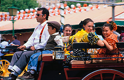 """Europe, Spain, Andalucia, Sevilla, family riding in horse-drawn carriage during """"Feria de Abril"""" festival, held annually in April"""