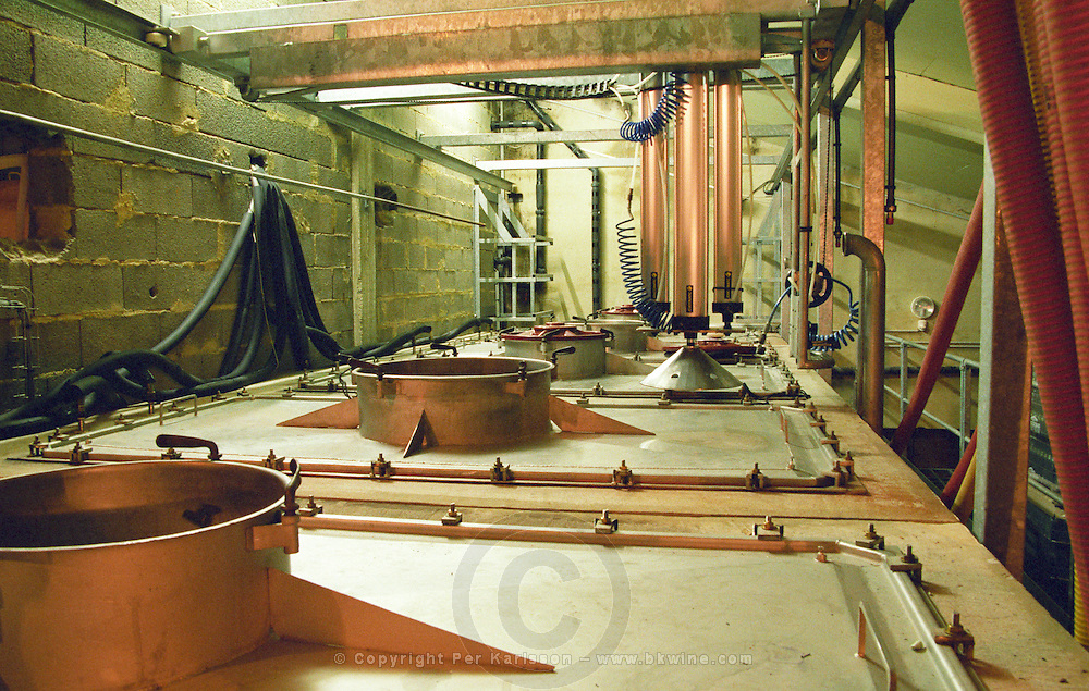 """In the winery, concrete fermentaion tanks with removable tops. A machine for pigeage, punching down of the grape skins and pips, the """"cap"""", to increase extraction.  Domaine Remejeanne Réméjeanne, Sabran, Gard France, Europe"""