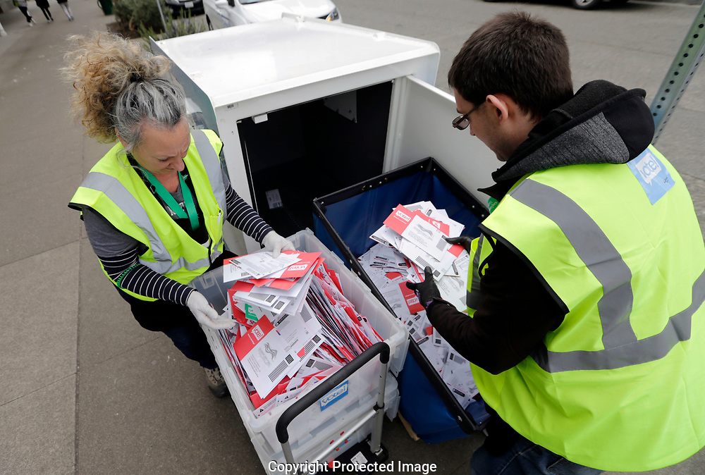 King County Election workers collect ballots from a drop box in the Washington State primary, Tuesday, March 10, 2020 in Seattle. Washington is a vote by mail state. (AP Photo/John Froschauer)