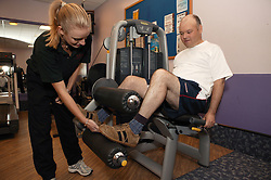 Access to services, Fitness instructor with disabled man in the gym; using Leg Curl,