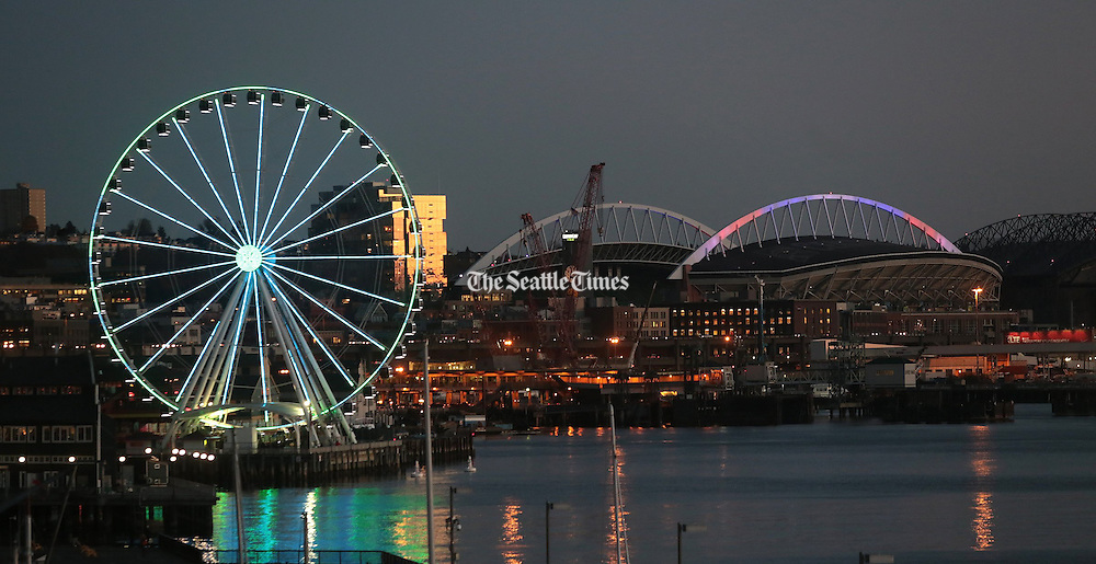 The Seattle Great Wheel glows in the early evening, along with CenturyLink Field. (Greg Gilbert / The Seattle Times)