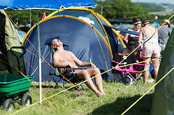 © Licensed to London News Pictures. 13/06/2014. Isle of Wight, UK.   A man relaxes in the early morning sun beside his tent  at Isle of Wight Festival 2014 - today is expected to be the hottest day of the year in the UK.   The Isle of Wight festival is an annual music festival that takes place on the Isle of Wight. Photo credit : Richard Isaac/LNP